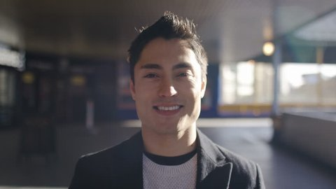 Portrait of handsome asian man looking to camera and smiling, in slow motion
