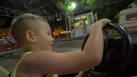 Excited boy having a fun ride in bumper car in amusement park. He driving and hitting others vehicles