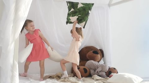 Children fight with pillows. Happy sisters are fighting with pillows.