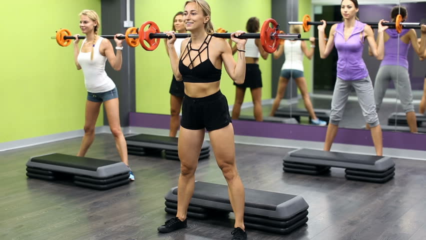 Group of females performing weight lifting workout at gym