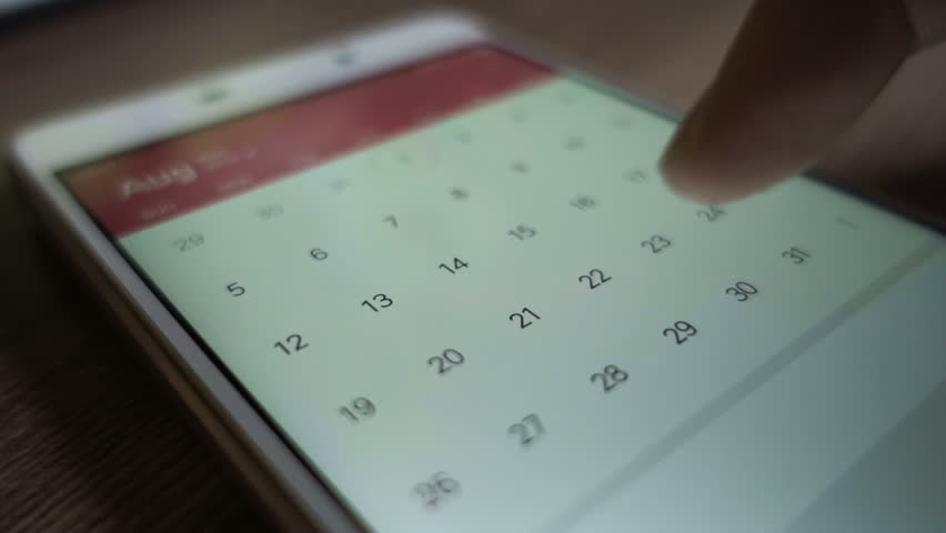 Man using calendar app on the mobile device closeup. Close-up male hands scrolling screen on smartphone.