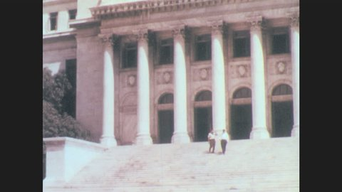 Puerto Rico 1960s: Men walk down steps of government building lined with columns. Government building. Two flagpoles, American flag and Puerto Rican flag flying.
