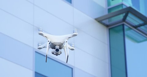 Modern drone quadcopter flying with business building in background
