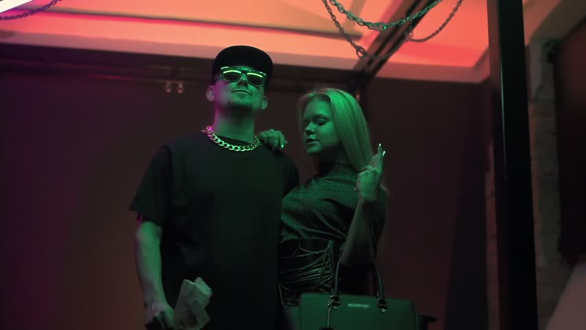 Hip hop caucasian man in sunglasses and spiked cap throws money with sexy girl in expensive clothes at colorful light studio | Shutterstock HD Video #1007175883
