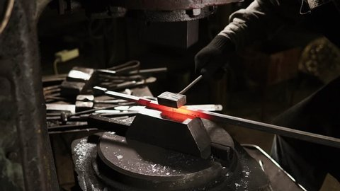 Process of forming red hot metal rod in a forge with automatic molder. Blacksmith is using metal instrument for smooth forms.