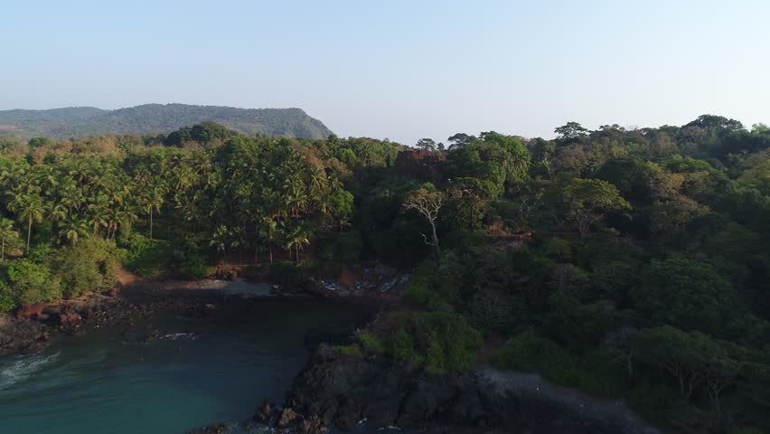 Flying over tower of Cabo De Rama Fort on high rocky coast. Aerial view.