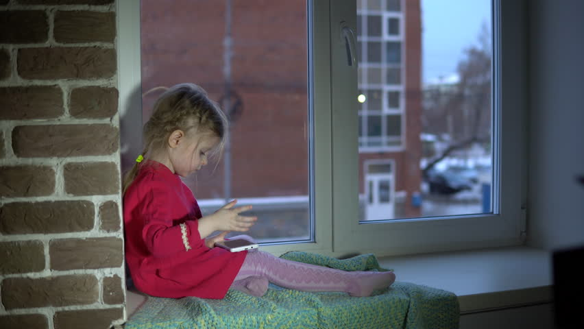 Little Cute Girl In Pink Dress Is Studying And Playing In App On White  Smartphone,