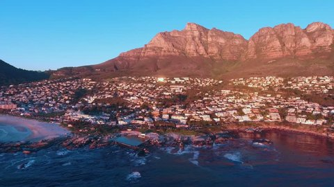 Aerial view from drone of Camps Bay in Cape Town South Africa at sunset with beach below and mountains behind.