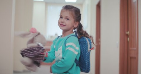 A little beautiful girl in a blue sweater and a pink skirt, with a ponytail, a toy hare in dress and a backpack runs along the corridor of the clinic and jumps, turns over and smile