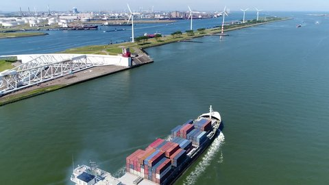 Aerial of container ship moving through Maeslantkering storm surge barrier showing heavy ship exhaust plume on Nieuwe Waterweg Netherlands barrier closes if city of Rotterdam is threatened by floods