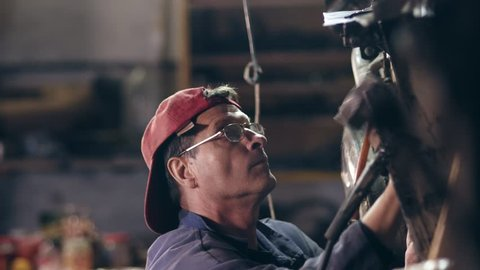 Male worker with glasses and red cap on at mechanical hangar adjusts something on metal construction with a hammer.