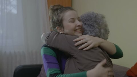 Young female student talking hugging and kissing good bye her senior grandmother teacher after visiting her at home
