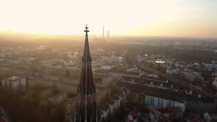 Aerial shot of the tip of a church in the Bavarian capital Munich during the sunset in the evening light