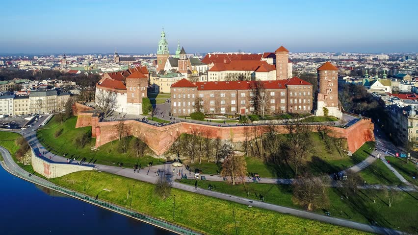 Royal Wawel Castle and Gothic Cathedral in Cracow, Poland, with Renaissance Sigismund Chapel with golden dome,  fortified walls, yard, park and tourists. Aerial view at sunset in winter