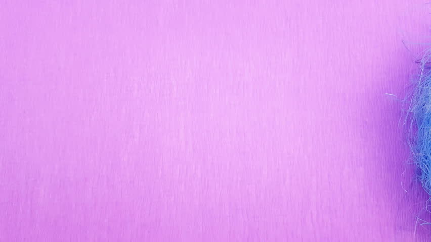 Yellow easter eggs in blue nest on purple background. Close up. | Shutterstock HD Video #1007266483