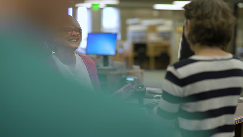 College librarian smiling and talking to students