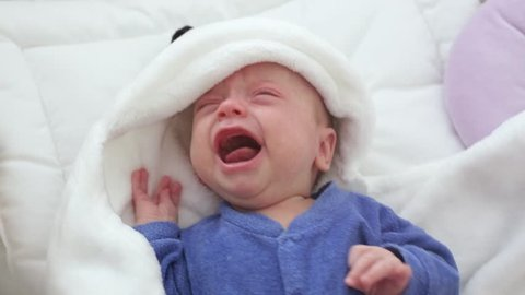 Newborn crying baby boy. New born child tired and hungry in bed under a blue knitted blanket.