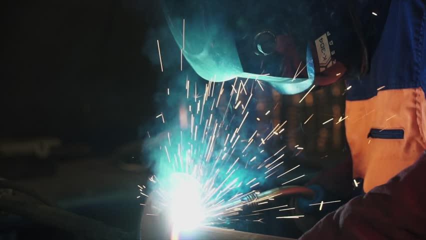 Welder at work in metal industry. Clip. Welder at work in factory. Welder welding a metal in workshop | Shutterstock HD Video #1007331313