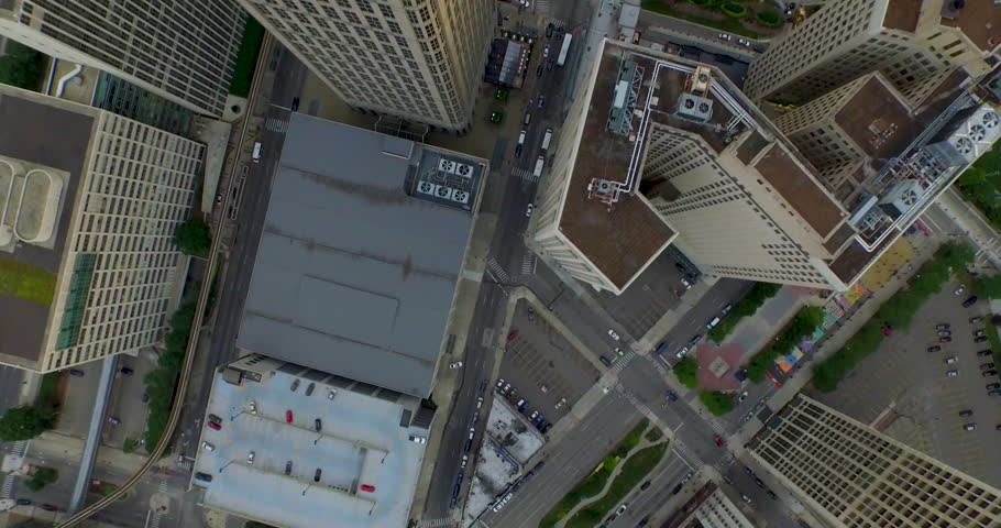 Aerial flyover tilt up over buildings in downtown Detroit.