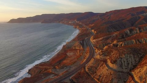 Flying south over the highway on the Baja Mexico Coastline in Ensenada during a beautiful Sunset.