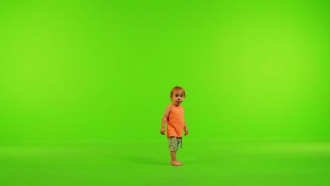 Cute little toddler walks happily from side to side, stops and eat in a full shot over a green screen.