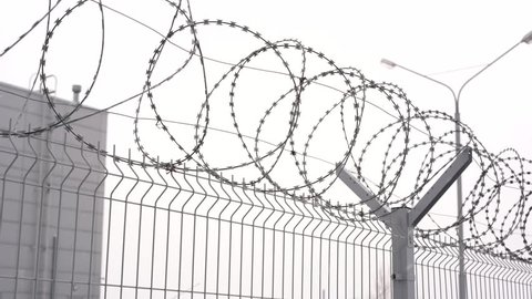 barbed wire on a fence in winter close-up. fencing of a restricted area or prison