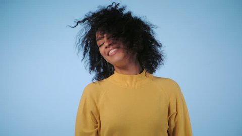 beautiful black woman with afro hair having fun smiling and dancing in studio against blue background. slow motion