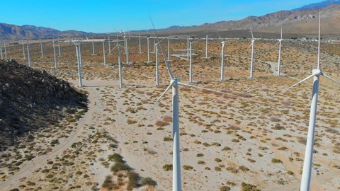 Aerial Drone Shot Flying Forward and Through a Still Wind Turbine amongst a Wind Turbine Farm with Mountains, Rocks, Grass and Blue Sky in View at Palm Springs, California