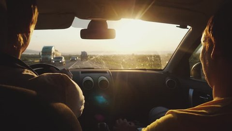 Man Driving a Car at Sunset. Beautiful Road with amazing lens flare effect. two friends are traveling in sunny day on summer vacation. slow motion. 1920x1080