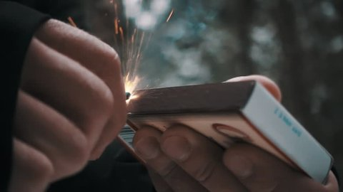 Male hand strikes match against box, burns it up creates lots of sparks outside in woods, slow motion close up shot