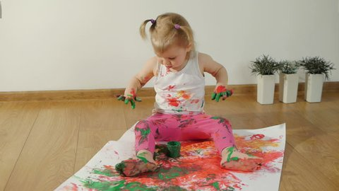 Little girl with smudgy paint fingers draws on a large sheet of white paper sitting on the floor