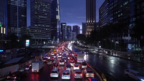 Time lapse of a traffic jam along the Sudirman avenue in the heart of Jakarta business district at night in Indonesia capital city. Construction works is for the new MRT station.