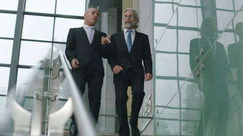 two corporate executives chatting while descending stairs in company.