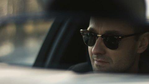 One stylish trendy guy driving the automobile on the route closeup. Motivation concept: successful smiling business person going to the workplace. Traffic, stress, daily routine