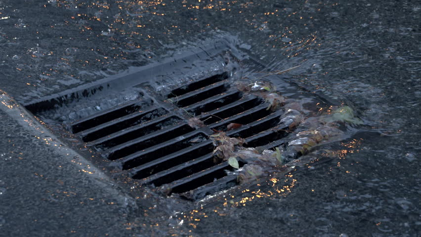 Storm Drain, Heavy Rain, Slow Motion, Close Up. Heavy rain pours into a storm drain.