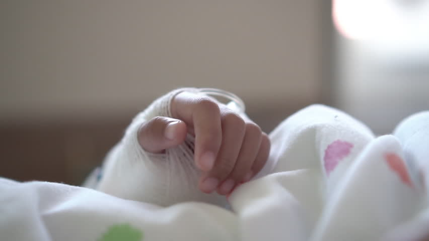 Closeup of sick asian child girl bandaged hand while lying down on bed in the hospital. Real time shot in treatment room.