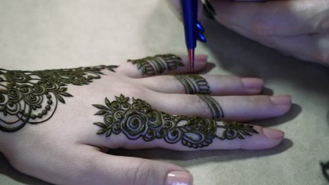 Woman hand being decorated with henna tattoo, mehendi