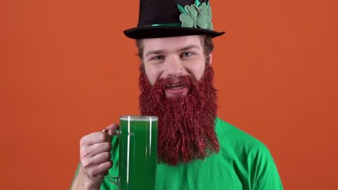 Young man celebrating saint patrick's day isolated on orange offering green beer