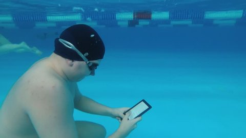 The guy is reading an electronic book underwater. This is a special waterproof electronic device. You can read the text and show signs directly underwater.
