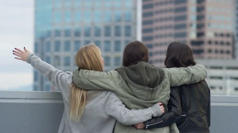 65023a6d58 arms around each other · Group Of Friends Look Out At City Views And Smile  At Each Other From Rooftop,