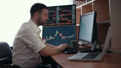Stockbroker in white shirt is working in a monitoring room with display screens. Stock Exchange Trading Forex Finance Graphic Concept. Businessmen trading stocks online.