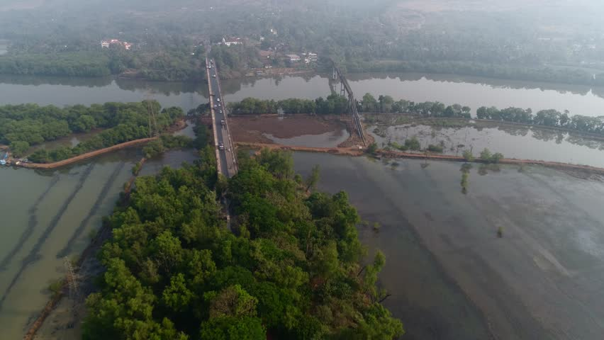 Flying over a large road bridge and aqueduct over the river in Goa, India. Aerial view at high altitude. | Shutterstock HD Video #1007525974