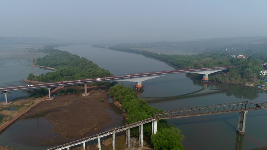 Flying over the bridge, cars moves on a large concrete bridge across the Zuari river in Goa, India. Aerial view. | Shutterstock HD Video #1007526007