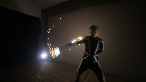 Artist on the stage juggles stick with fireworks. LED show