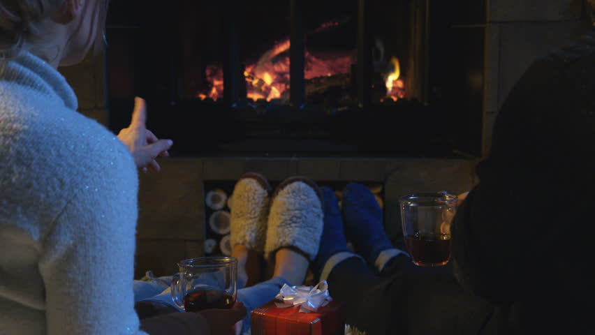 Romantic couple relaxing on the floor in front of a burning log fire in winter with a view from behind of their feet in slippers as they chat and sip coffee or gluhwein with a Christmas gift between.