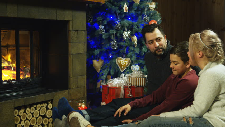 Middle view of young family relaxing on a shaggy rug in front of a burning fire and Christmas tree with burning candles as they spend time together. Shot on Red cinema camera.