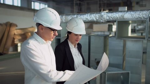 Construction engineers workers, teamwork working with blueprint 4 k Business team in site. Man and woman engineers discussing looking at drawing engineer architects businesswoman businessman factory