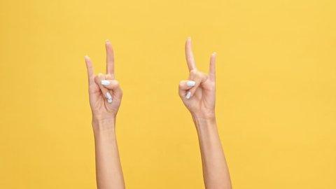 Woman hands showing rock gestures over yellow background