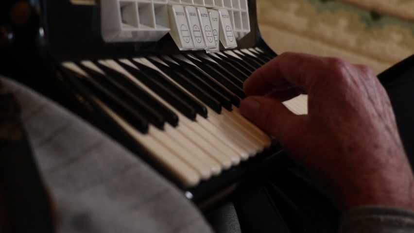 Playing the accordion. Hands playing music on a key board shot over the shoulder.  #1007594053
