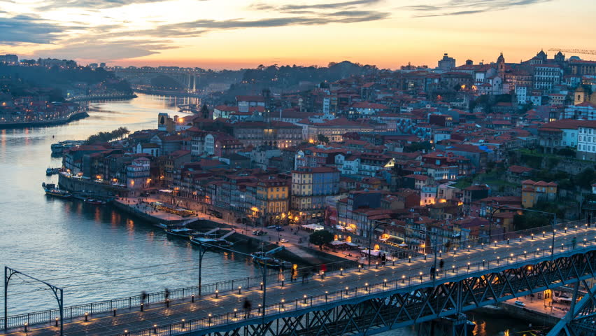 Amazing Porto Timelapse at sunset, old city with river Douro in the foreground. Boats passing by with the Arrabida bridge in the distance and the Dom Luis bridge on the right turning on the lights | Shutterstock HD Video #1007599183